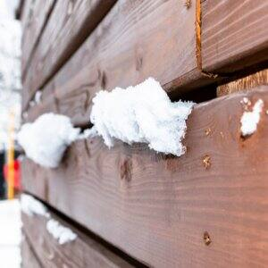 Wooden fence outside in snow (Photo by Emily Faith Snell / Shutterstock.com)