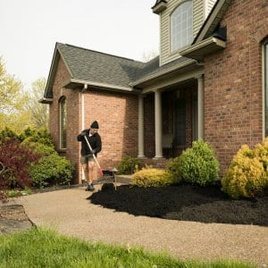front of red brick house with bushes and mulch (Photo by  wanderluster/E+ via Getty Images)