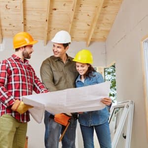 three adults in hard hats smile and look over renovation plans in a partially finished room (Photo by Robert Kneschke - stock.adobe.com)