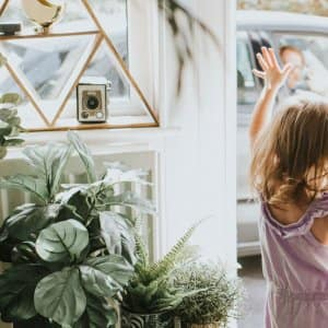 A girl waving out the front door on a summer day (Photo by Catherine Falls Commercial/Moment via Getty Images)