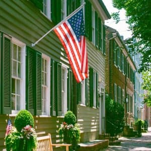 A row of green townhouses with exterior shutters (Photo by Grace Cary/Moment via Getty Images)
