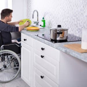 Man in wheelchair washes dishes (Photo by Andrey Popov - stock.adobe.com)
