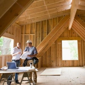 Home builders discuss plans in attic of framed house (Photo by Ed Bock / The Image Bank via Getty Images)