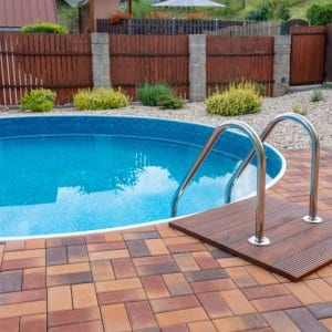 small round home swimming pool with silver stairs and brick patio (Photo by ArtushFoto - stock.adobe.com)