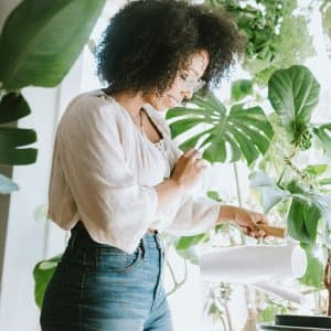 Young Woman Waters Her Houseplants (Photo by RyanJLane / E+ via Getty Images)
