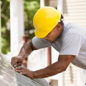 A man in construction gear installing roof flashing (Photo by Huntstock / Brand X Pictures via Getty Images)