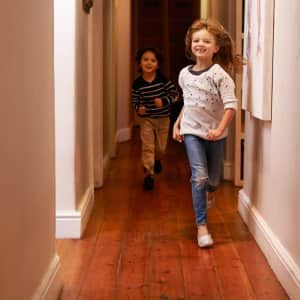 Kids running down hardwood floors (Photo by PeopleImages / E+ via Getty Images)