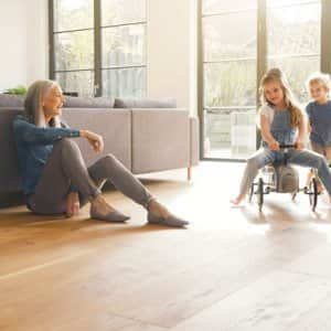 grandmother playing with kids on hardwood floor in living room (Photo by  Westend61 via Getty Images )