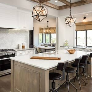 A luxurious kitchen with an island and pendant lights (Photo by hikesterson/iStock / Getty Images Plus via Getty Images)