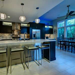 A kitchen with bar and large pendant lights with white globes