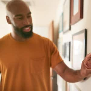 man smils and adjusts thermostat on waall (Photo by Monkey Business - stock.adobe.com)