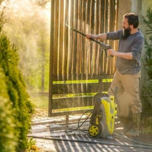 A man cleaning a wooden gate using a pressure washer (Photo by Andrea Obzerova / EyeEm/EyeEm via GettyImages)