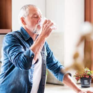 Senior man cooling off with drink of water (Photo by Halfpoint / Shutterstock.com)