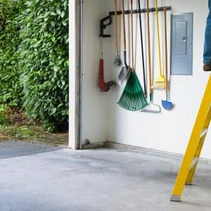 A man standing on a ladder inside his home's garage (Photo by Don Mason/The Image Bank via Getty Images)