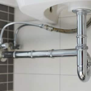 metal sink siphon and drain in white bathroom (Photo by vladdeep - stock.adobe.com.)