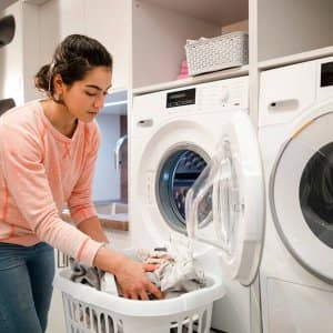 Person doing laundry at home (Photo by SolStock/E+ via Getty Images)