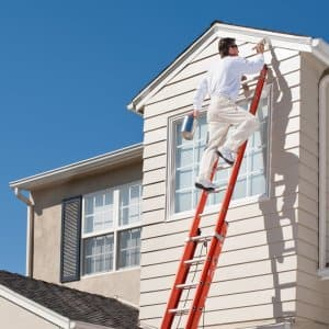 A professional standing on a ladder paints the exterior of a house (Photo by Spiderstock/E+ via Getty Images)