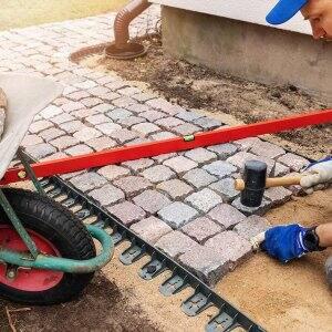 Professional paver laying sidewalk (Photo by ronstik - stock.adobe.com)