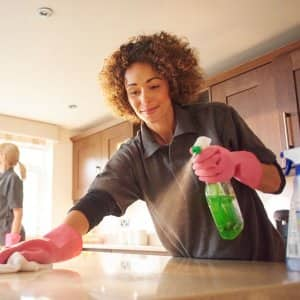 Two professionals cleaning a house's kitchen (Photo by sturti/iStock / Getty Images Plus via Getty Images)