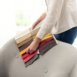 Professional decorator choosing the best upholstery for the armchair by holding fabric samples against it (Photo by StockPhotoPro - stock.adobe.com)