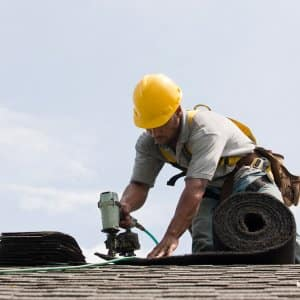 Man installs shingles to roof (Photo by Huntstock / Brand X Pictures via Getty Images)