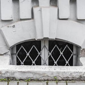 basement window with wire bars sits behind stone square egress with decorative stone details above window (Photo by Dobrydnev - stock.adobe.com.)