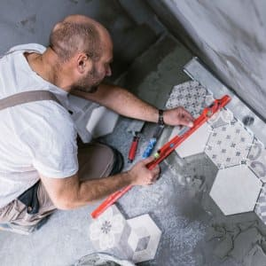 Tiler measuring and leveling the bathroom floor (Photo by Mixmike / E+ via Getty Images)