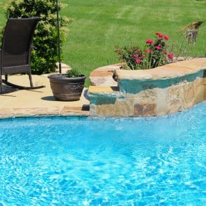 closeup of swimming pool with stone edge, concrete patio, and black lawn chair (Photo by tammykayphoto - stock.adobe.com)