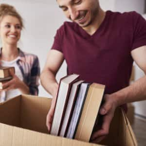 Couple packing books into boxes
