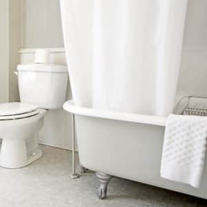 shot in white bathroom of white toilet and partial view of bathtub with white accents (Photo by  Marlene Ford/Moment via Getty Images)