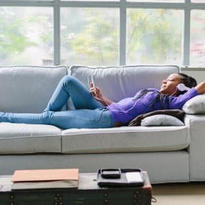 Woman wearing headphones lying down on sofa (Photo by Innocenti / Cultura via Getty Images)