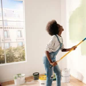 a woman in overalls painting a white wall with green paint and smiling (Photo by © VAKSMANV - stock.adobe.com)