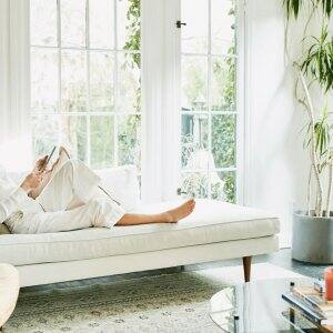 A woman relaxing on sofa in a bright living room (Photo by Thomas Barwick/DigitalVision via Getty Images)