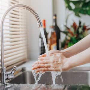 A woman washing her hands in kitchen sink (Photo by interstid - stock.adobe.com)