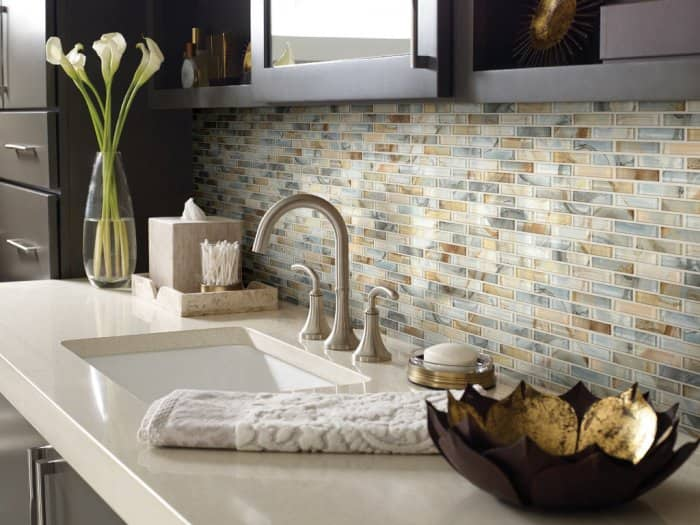 The blue tones of this tile backsplash complement the tans and browns of the other tiles, the counter and the cabinets. (Photo courtesy of Shaw Floors)