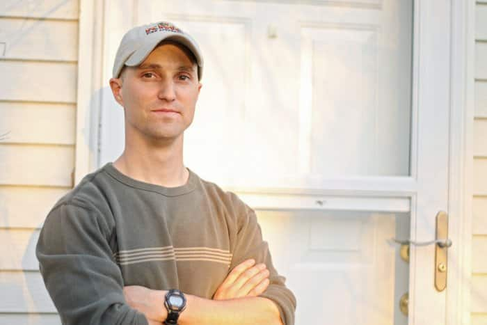 man wearing baseball cap and brown shirt with arms crossed in front of door