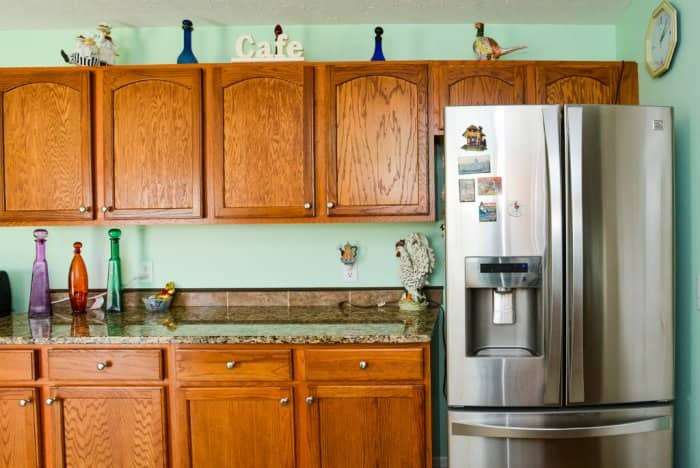 A kitchen with brown cabinets and a stainless steel refrigerator