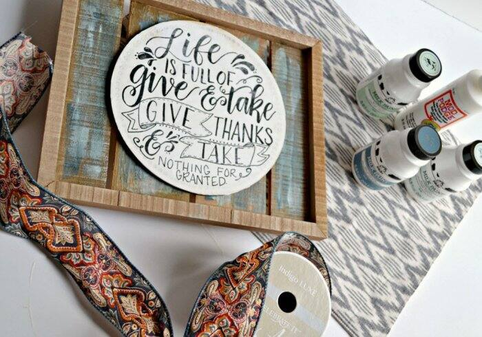 Grab a wood pallet sign, a small round plaque, some paint, photo transfer mod podge and ribbon to make this beautiful sign for your home.