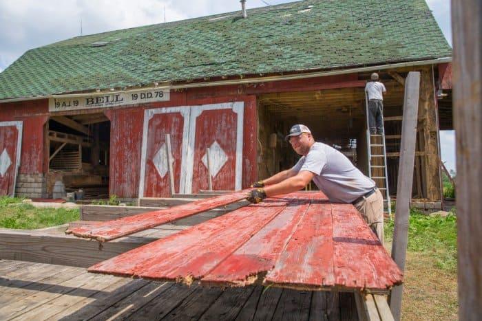 Hoosier Reclaimed Timber owner Adam Dick stacks wood from a barn in Kokomo, Indiana