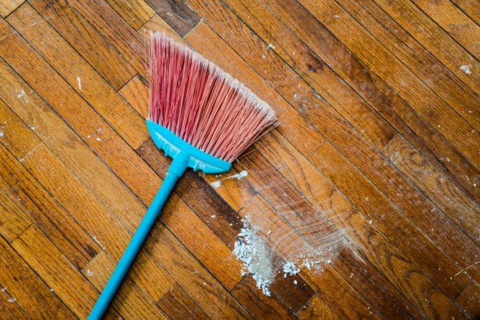 broom on dirty, dusty wood floor