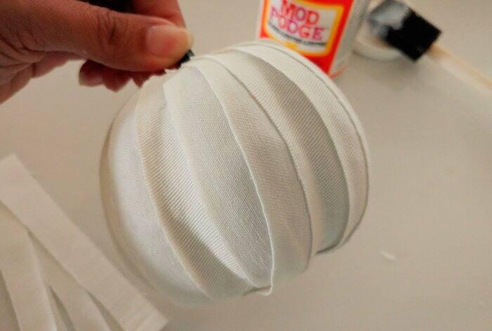 decoupaging white fabric strips to craft pumpkin