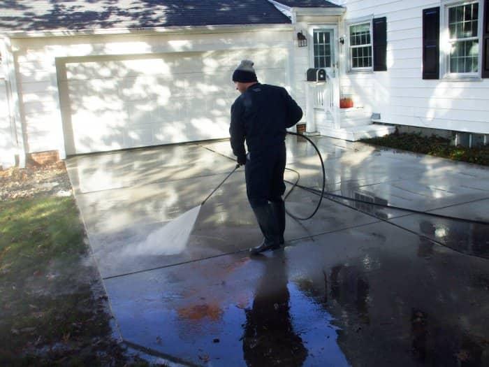 man pressure washing dirty concrete driveway