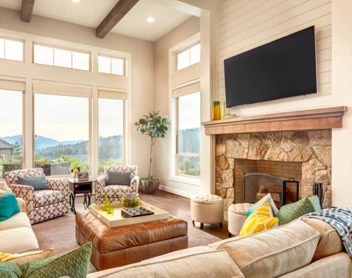 TV mounted above wood and stone fireplace mantel