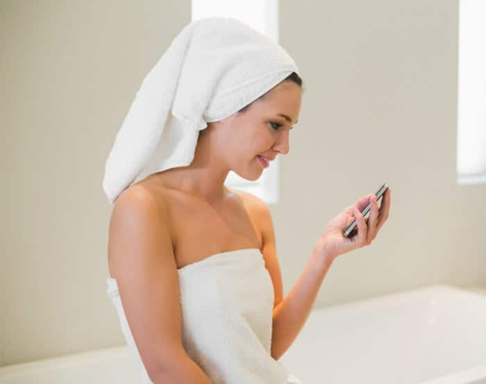 Woman in towel looking at her mobile device