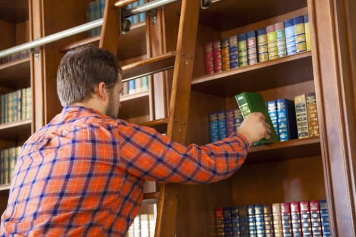 man on ladder in book library
