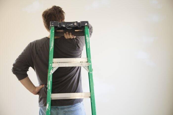 painter holding ladder behind back