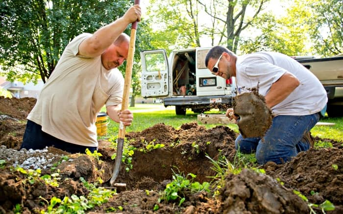 men digging trench in lawn