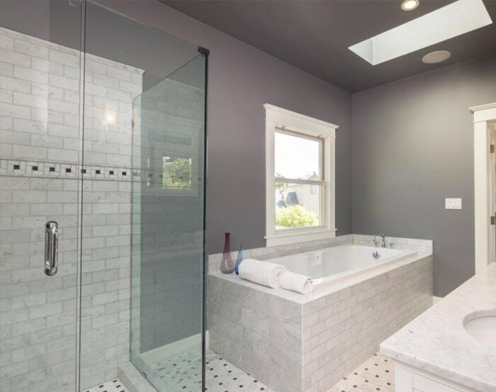 Frameless shower door alongside tiled bathtub