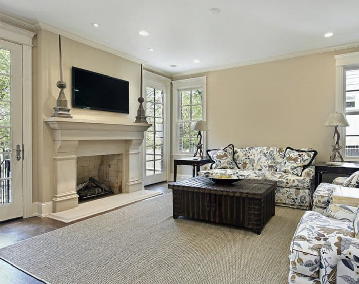 White, painted fireplace with two art sculptures flanking the TV mounted above