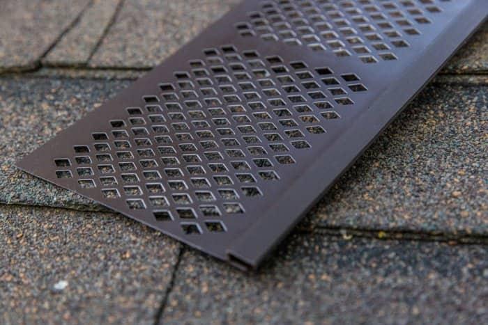 vinyl gutter guard sitting on asphalt roof